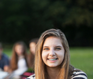 Teenage girl with dental braces smiling in Hamilton park