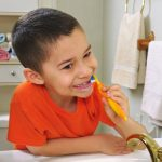 Young child brushing teeth with child-friendly toothbrush