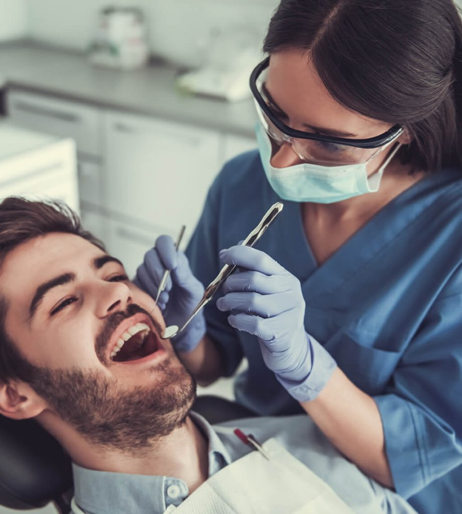 Hamilton dental hygienist using dental mirror to check bearded patient for cavities