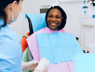Hamilton dentist greeting smiling teenage girl in grey sweater and dental bib